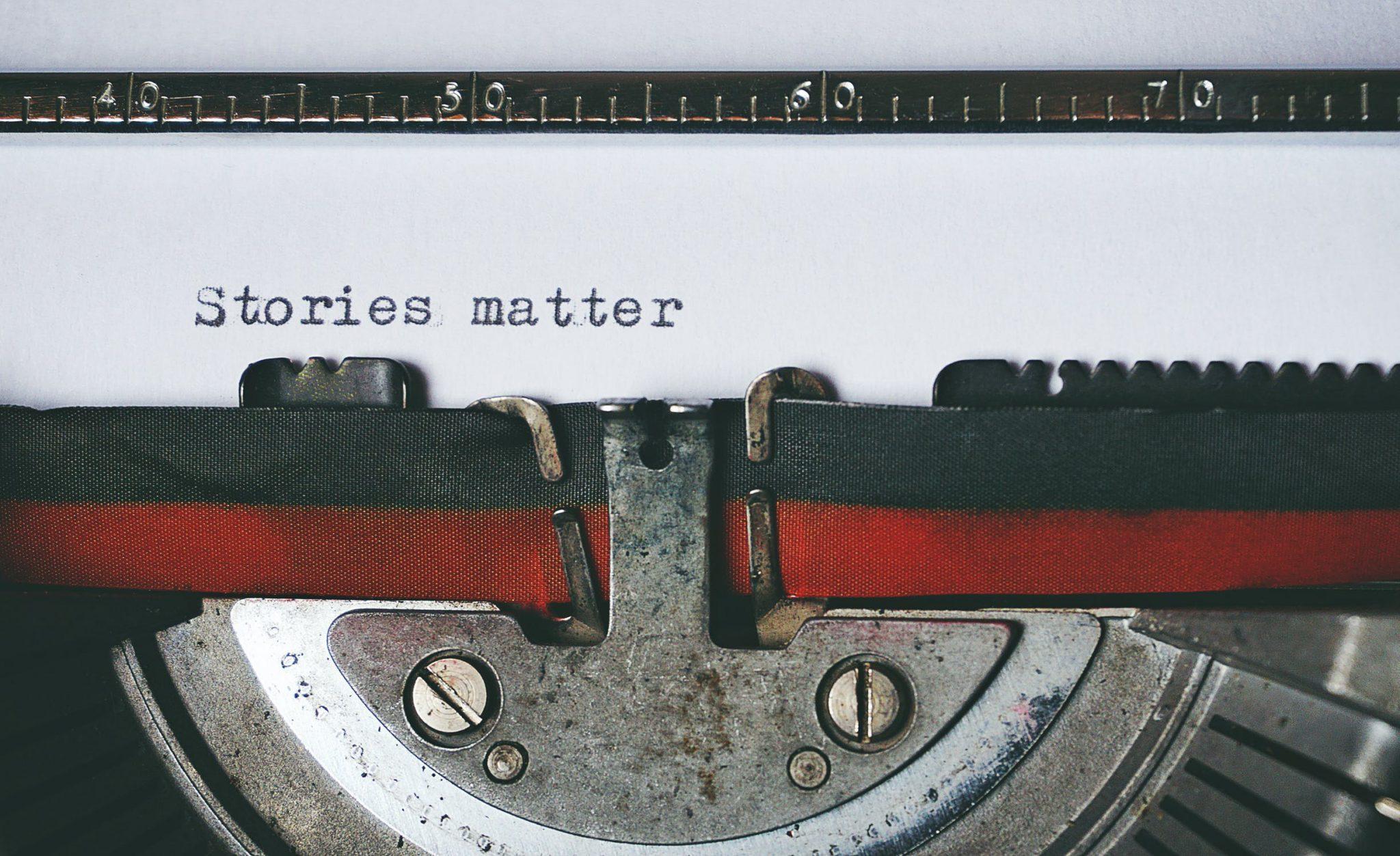 """Spannende Wendungen schreiben; Papier in Schreibmaschine; auf dem Papier steht """"Stories matter"""""""