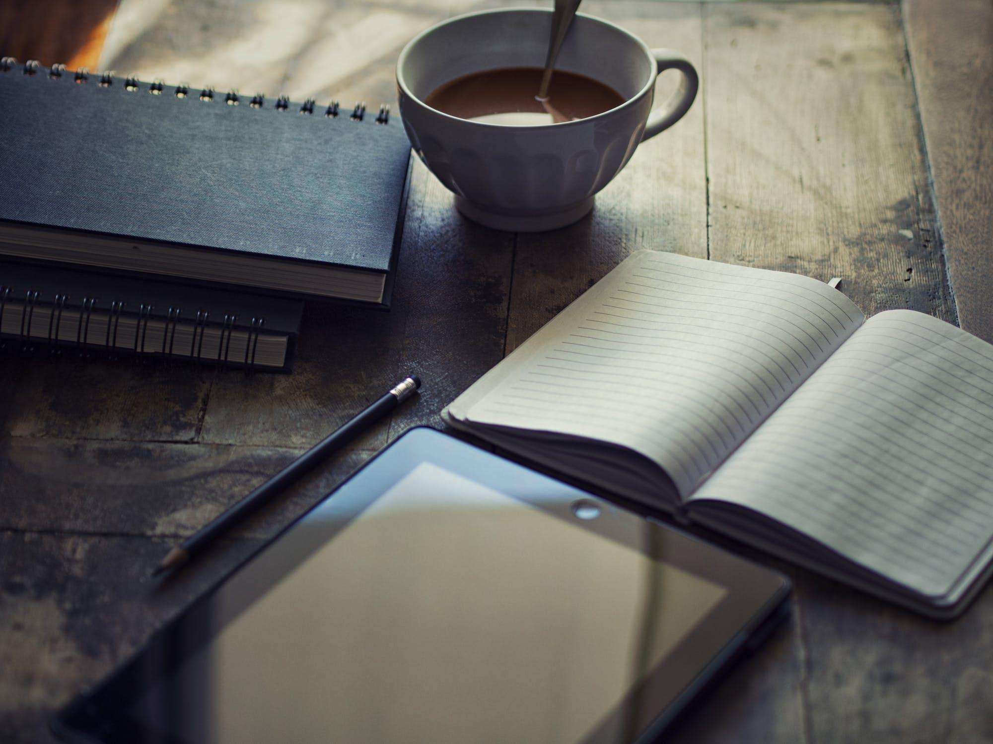 Fortsetzung schreiben; gemütlicher Tisch mit Kaffee, Notizbüchern, Stift und Tablet, Blog