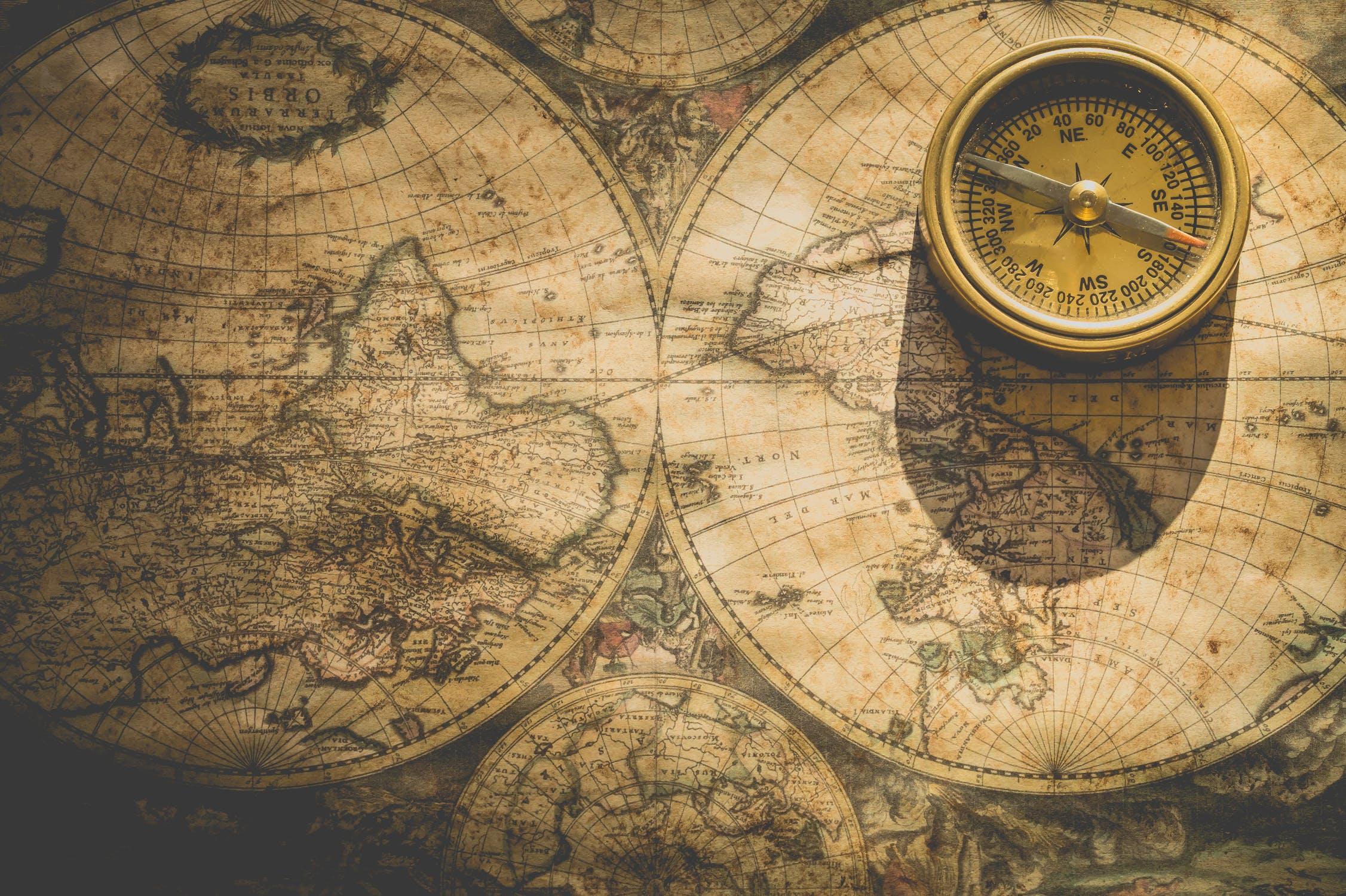 Alte etwas vergilbte Weltkarte mit Illustrationen; darauf liegt ein altmodischer Kompass; eigene Welt erschaffen