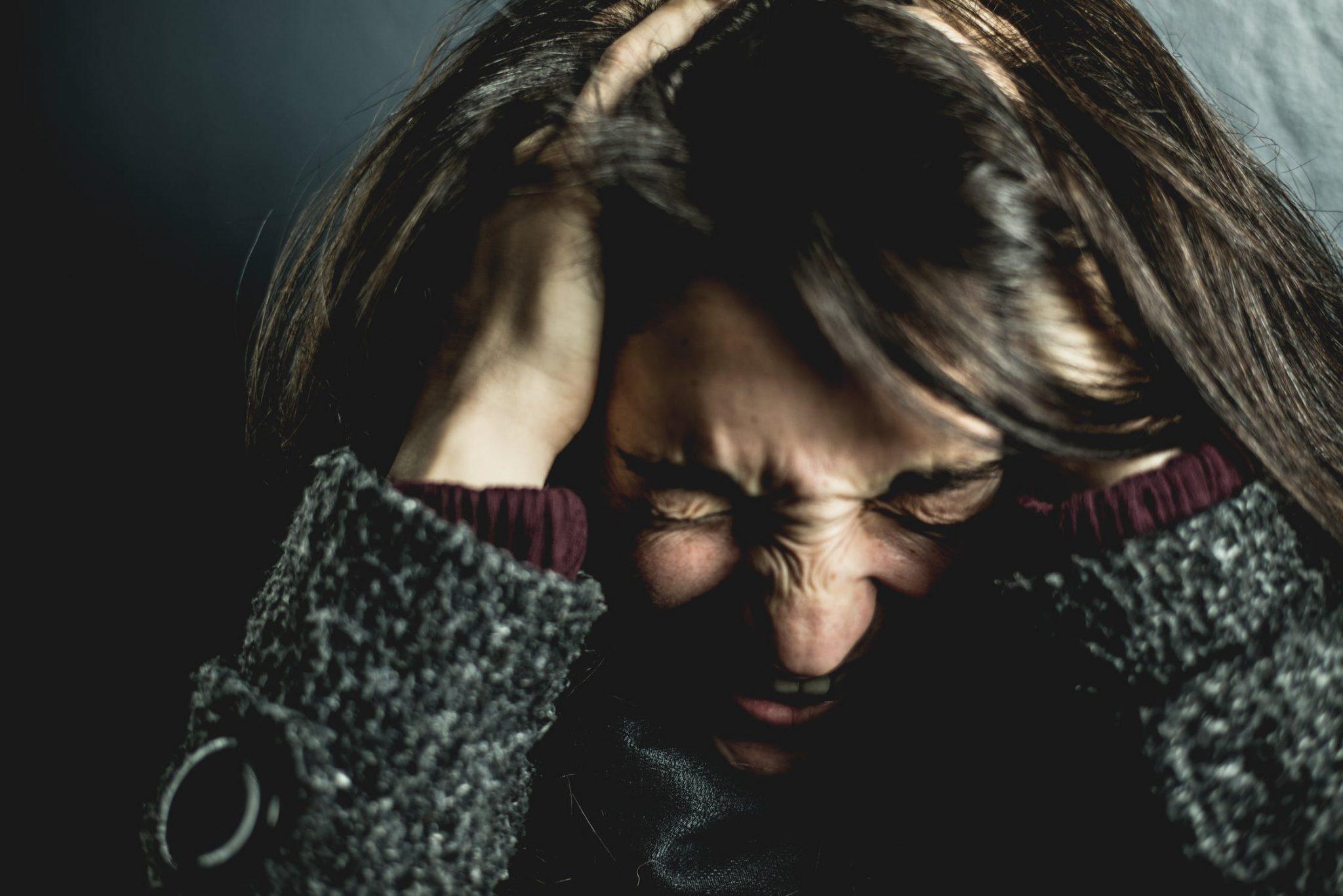 Mit Kritik umgehen; Frau hält sich verzweifelt den Kopf